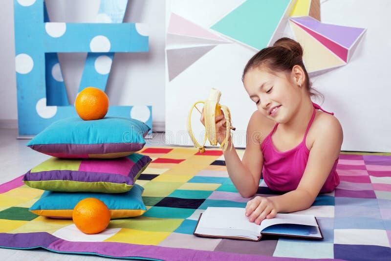 Mooi kindmeisje die en een banaan lezen eten Het concept van royalty-vrije stock foto