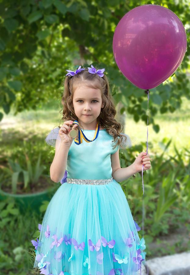 Mooi kindmeisje in elegante kleding met gouden medaille en luchtimpuls royalty-vrije stock afbeelding