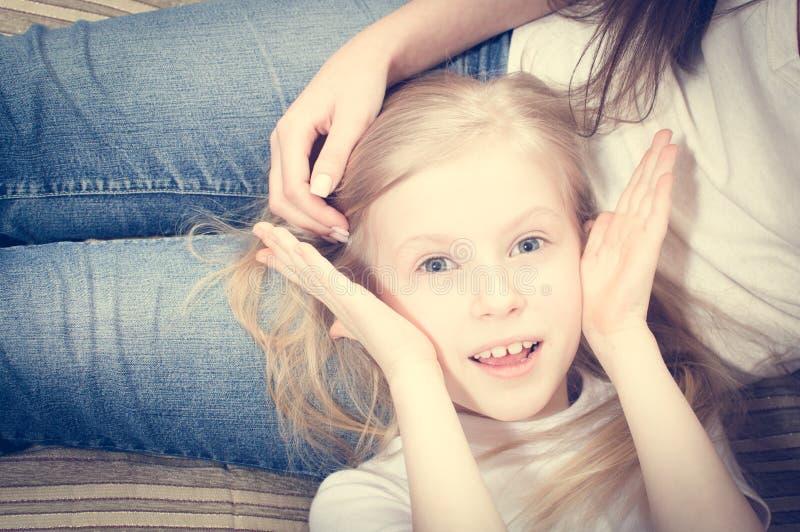 Mooi kindmeisje met het blauwe ogen glimlachen die op vrouwenknieën liggen royalty-vrije stock afbeelding