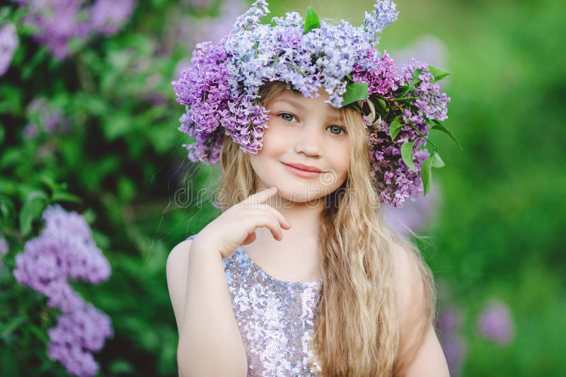 Mooi kindmeisje met kroon van lilac bloemen royalty-vrije stock afbeelding