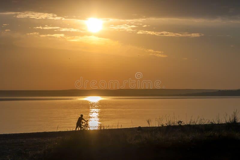Mooi kleurrijk de zomer overzees zonsopganglandschap met een blauwe hemel En de onherkenbare mens met een fiets silhouetteert stock afbeelding