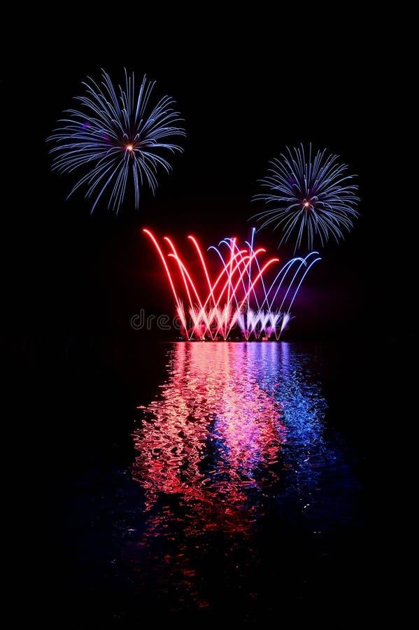 Mooi kleurrijk vuurwerk op de waterspiegel De sc?ne van de nacht Concept voor vakantie en vieringen stock afbeeldingen