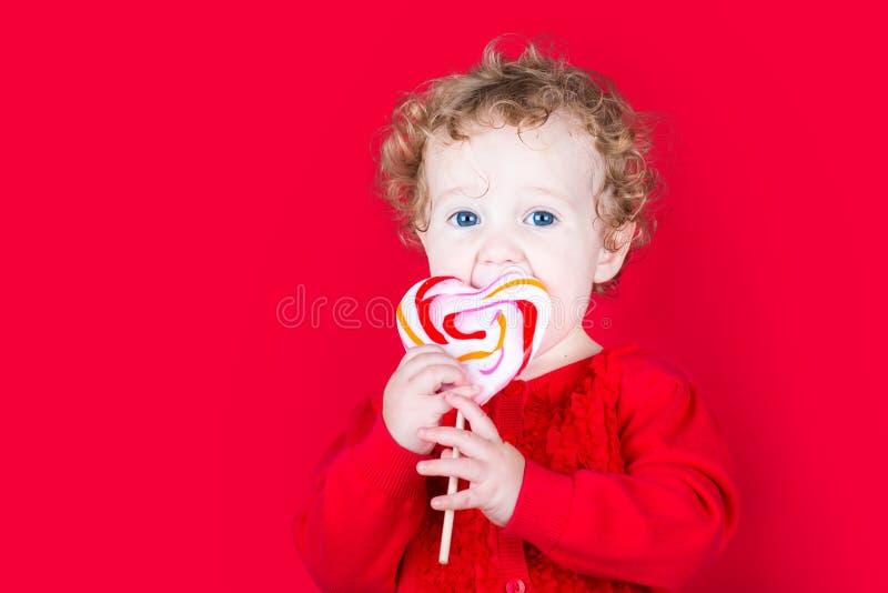 Mooi krullend babymeisje die een hart gevormd suikergoed op rode bac eten stock foto