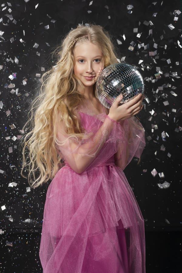 Mooi krullend het kindmeisje die van de blondetiener roze luchtdr. dragen stock afbeeldingen
