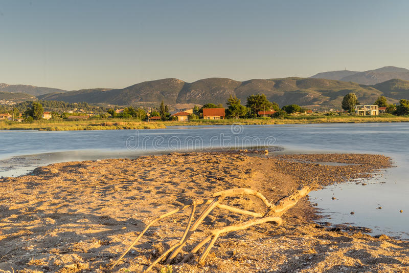 Mooi landschap bij het moerasland van Oropos in Griekenland met traditionele oude en kleurrijke huizen tegen het meer royalty-vrije stock afbeeldingen