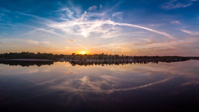 Mooi landschap met bezinning, blauwe hemel en geel zonlicht in zonsopgang stock foto