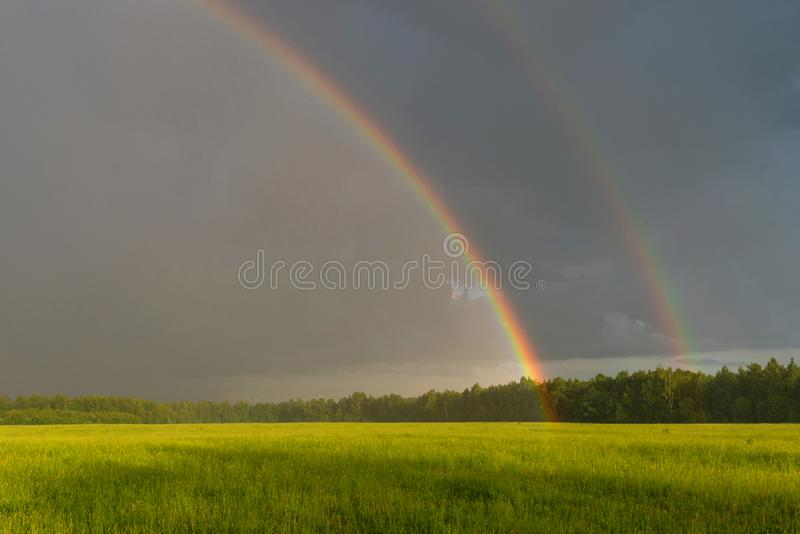 Mooi landschap met een dramatische hemel en een dubbele regenboog Groen gebied onder bewolkte hemel met dubbele regenboog royalty-vrije stock afbeelding