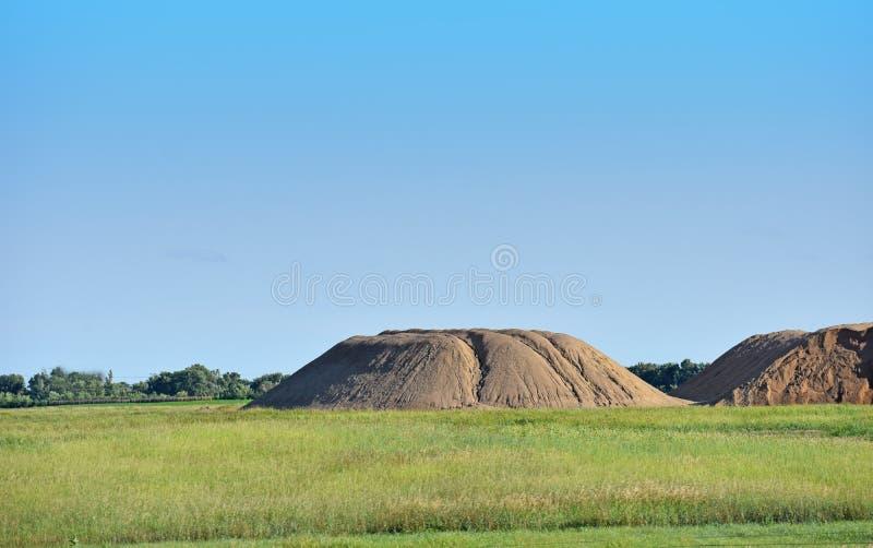 Mooi Landschap met groen gras, geel zand en blauwe hemel royalty-vrije stock afbeelding