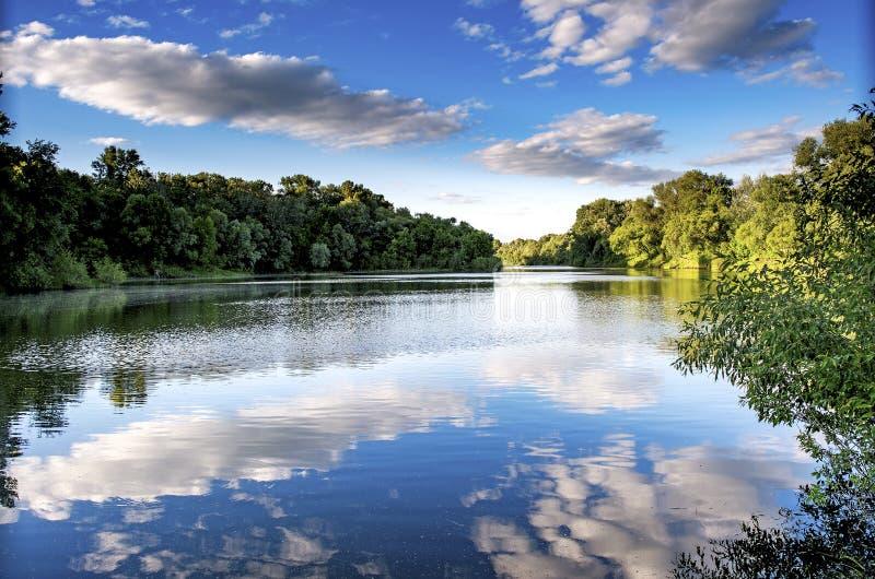 Mooi landschap met rivier onder de blauwe hemel met wolken stock afbeelding