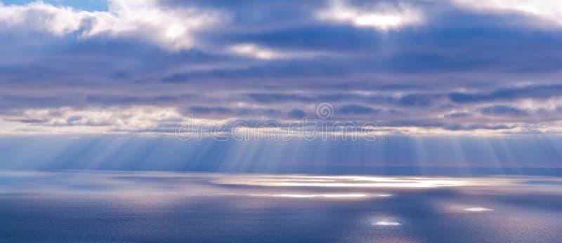 Mooi landschap met wolken en zonnestralen in blauwe en roze colo stock foto