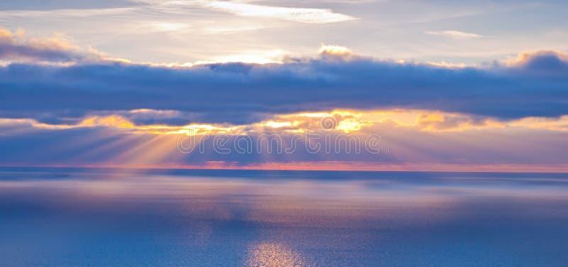 Mooi landschap met wolken en zonnestralen in mede blauw en sinaasappel stock fotografie