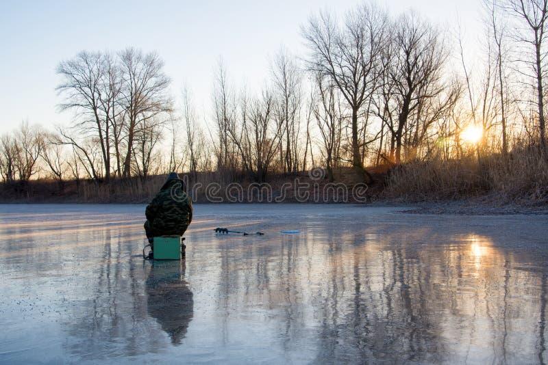 Mooi landschap van bosmeer Visserszitting op het ijs stock afbeelding