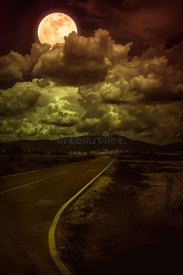 Mooi landschap van donkere hemel met heldere volle maan achter wolken en asfaltrijweg door streek in de voorsteden Sereniteitsaar stock foto