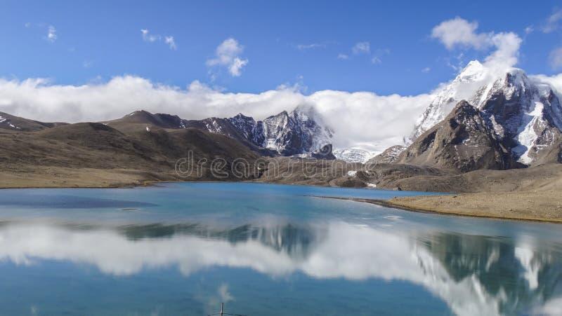 Mooi landschap van enorm hemelberg en meer met bezinning van wolk in schoon groenachtig water stock afbeeldingen