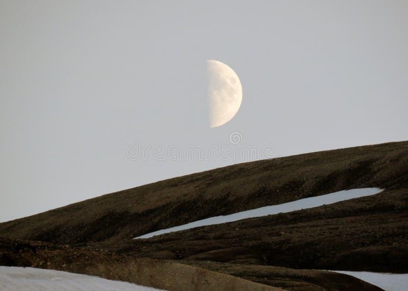 Mooi landschap van Landmannalaugar met sneeuw en in de was zettende maan, op de bovenkant van de berg Blahnukur tijdens de zonson stock afbeeldingen