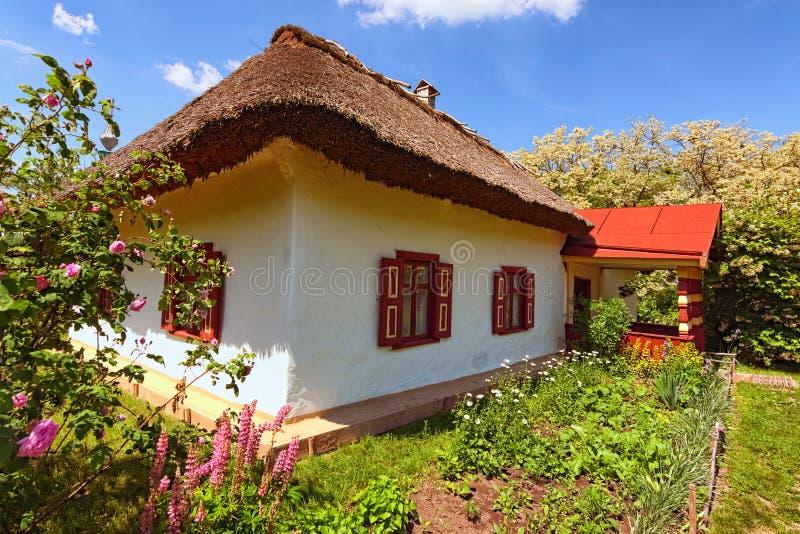 Mooi landschap van oud kleihuis met bloembed in zonnige de lentedag Museum pereyaslav-Khmelnitsky royalty-vrije stock foto's