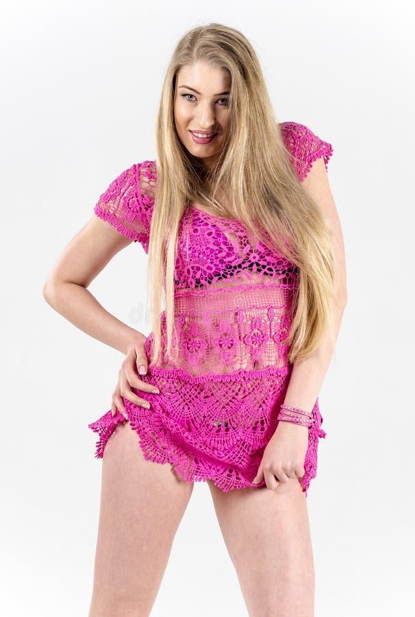Mooi langharig blonde in een roze kleding die het weelderige, flirty rok opheffen bevinden zich royalty-vrije stock fotografie