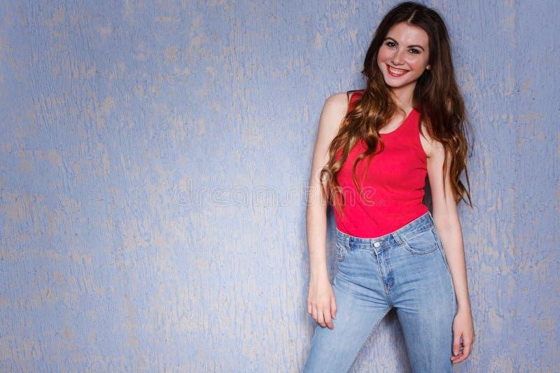 Mooi langharig meisje in jeans en het roze T-shirt stellen tegen een lilac textuurmuur stock fotografie