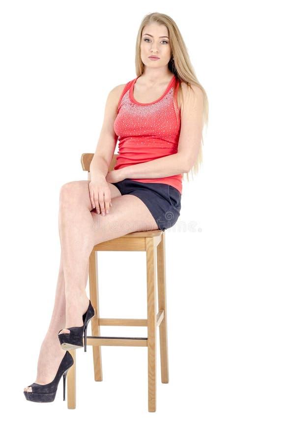 Mooi langharig vrolijk meisje in een korte rokzitting op een stoel en het gesturing stock foto's