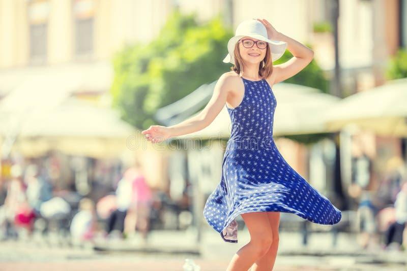Mooi leuk jong meisje die op de straat van geluk dansen Leuk gelukkig meisje in de zomerkleren die in de zon dansen stock fotografie