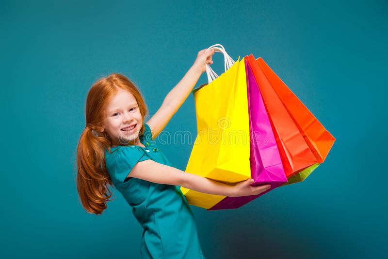 Mooi, leuk meisje in blauwe kleren met de lange rode verschillende pakketten van haarzorgen royalty-vrije stock afbeeldingen