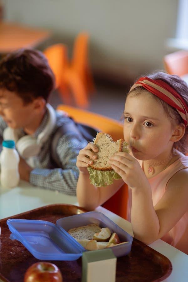 Mooi leuk schoolmeisje die heerlijke sandwich in kantine eten royalty-vrije stock fotografie