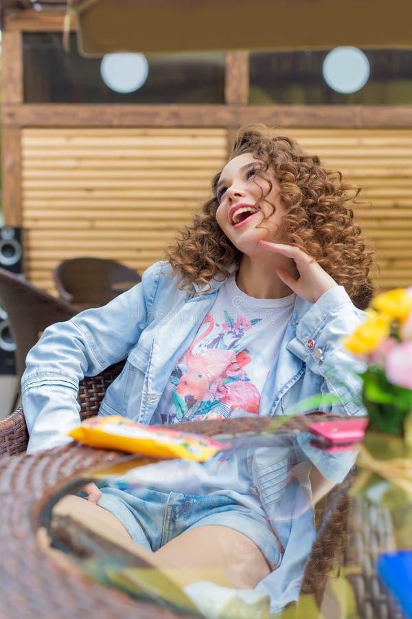 Mooi leuk vrolijk meisje in een heldere kleding met krullend haar en heldere samenstellingszitting bij een openluchtkoffie en wac stock fotografie