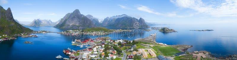 Mooi luchtpanorama van het blauwe overzees die het visserijdorp en de rotsachtige pieken Reine, Moskenes, Lofoten, zonnig Noorweg royalty-vrije stock foto