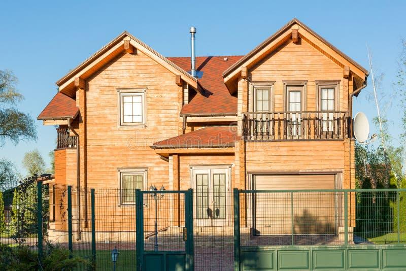Mooi luxe groot blokhuis De villa van het houtplattelandshuisje met met groen gazon, tuin en blauwe hemel op achtergrond royalty-vrije stock fotografie