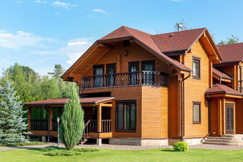 Mooi luxe groot blokhuis De villa van het houtplattelandshuisje met met groen gazon, tuin en blauwe hemel op achtergrond royalty-vrije stock afbeelding