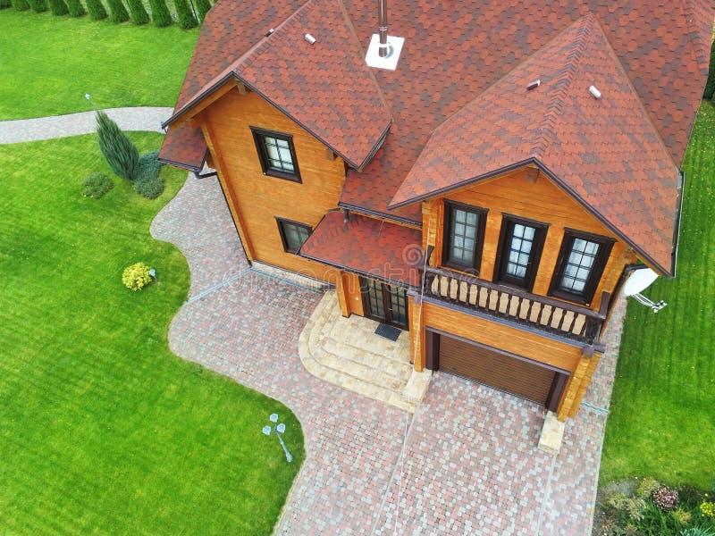 Mooi luxe groot blokhuis De villa van het houtplattelandshuisje met met groen gazon, tuin en blauwe hemel op achtergrond stock fotografie