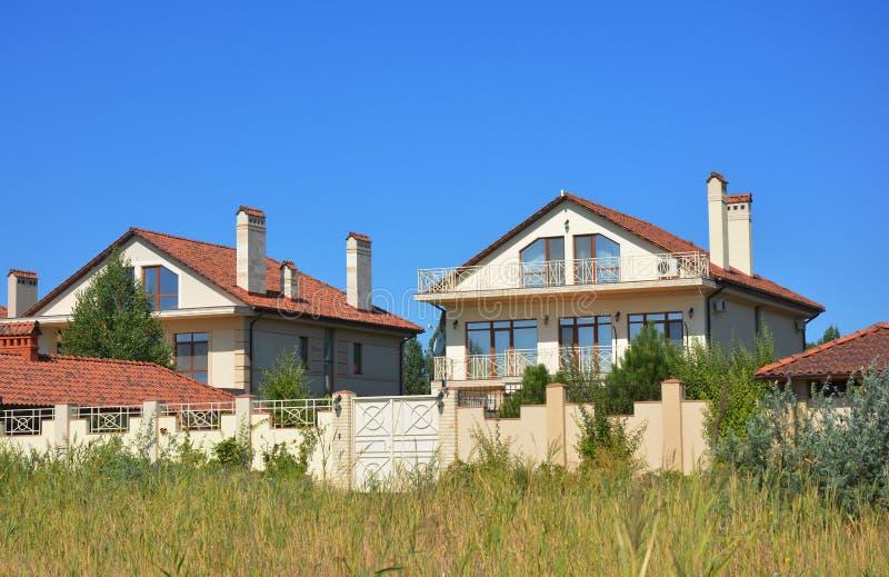 Mooi luxe modern huis in de voorsteden met kleidak, balkon, omheining, schoorsteen, garage, terras en tuin stock fotografie