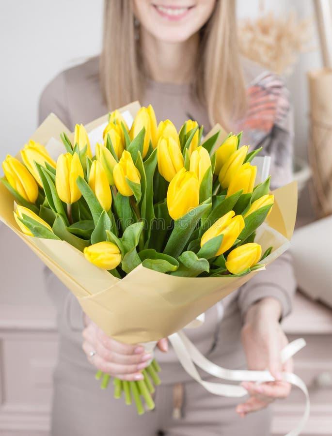 Mooi luxeboeket van gele tulpenbloemen in vrouwenhand het werk van de bloemist bij een bloemwinkel leuke mooi stock foto