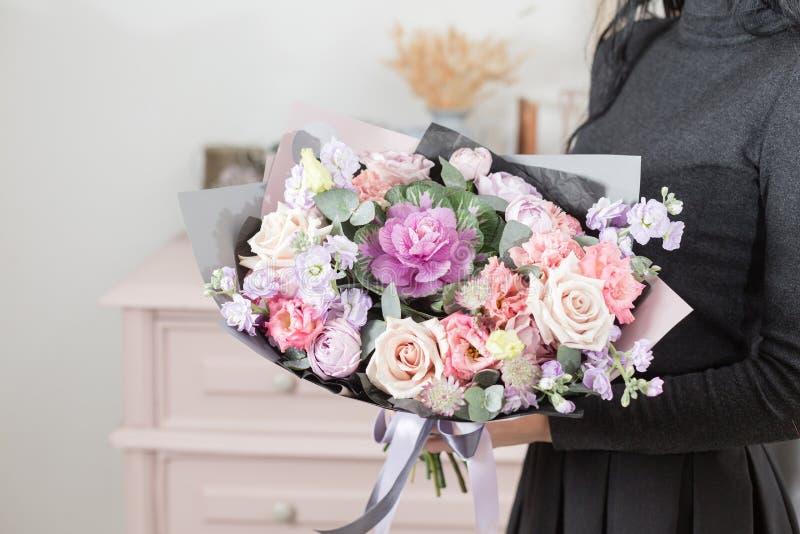 Mooi luxeboeket van gemengde bloemen in vrouwenhand het werk van de bloemist bij een bloemwinkel stock foto