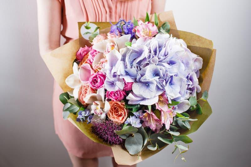 Mooi luxeboeket van gemengde bloemen in vrouwenhand het werk van de bloemist bij een bloemwinkel royalty-vrije stock afbeelding