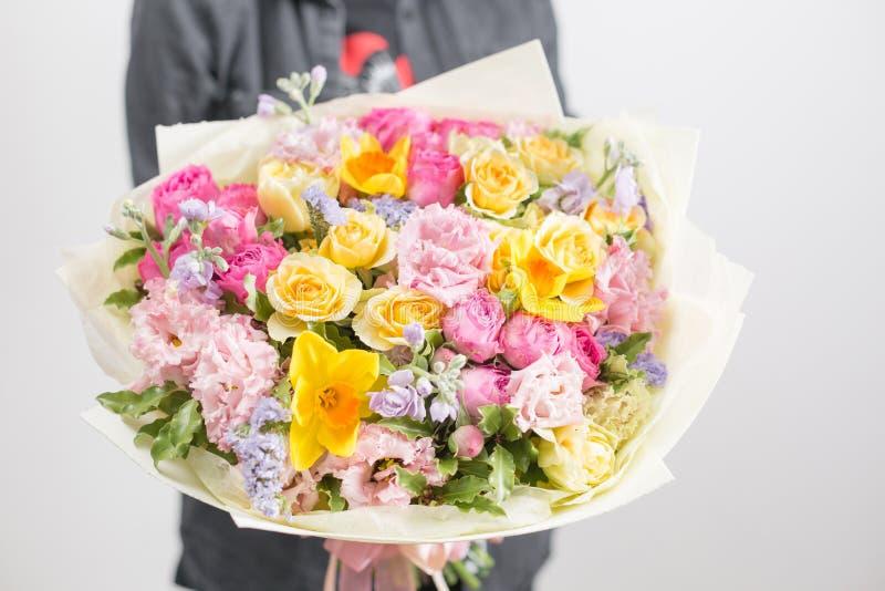 Mooi luxeboeket van gemengde bloemen in vrouwenhand het werk van de bloemist bij een bloemwinkel Een kleine familie stock fotografie