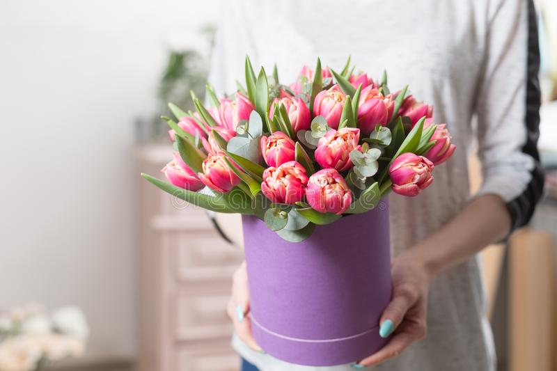 Mooi luxeboeket van roze tulpenbloemen in vrouwenhand het werk van de bloemist bij een bloemwinkel stock fotografie