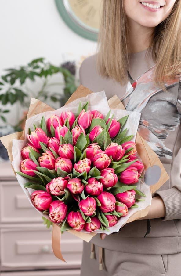 Mooi luxeboeket van roze tulpenbloemen in vrouwenhand het werk van de bloemist bij een bloemwinkel leuke mooi stock afbeelding