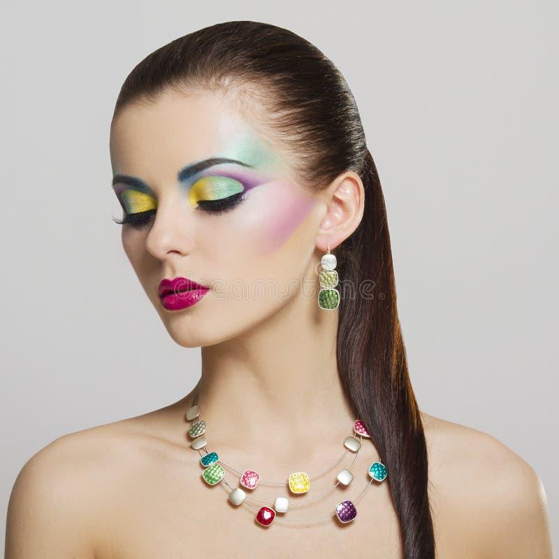 Mooi manierportret van jonge vrouw met heldere kleurrijke make-up stock foto's
