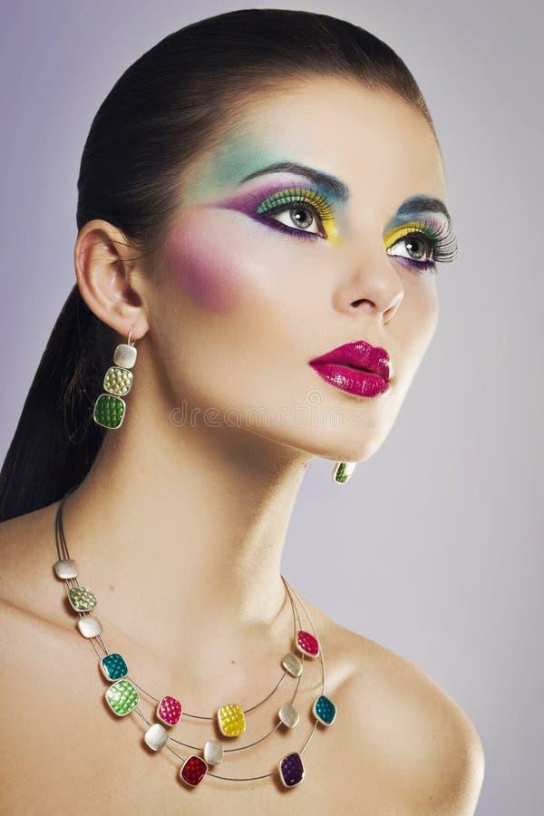 Mooi manierportret van jonge vrouw met heldere kleurrijke make-up stock foto
