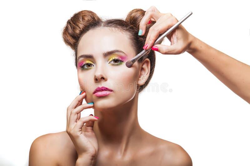 Mooi mannequinmeisje de van wie make-upkunstenaar make-up, e toepast stock afbeeldingen