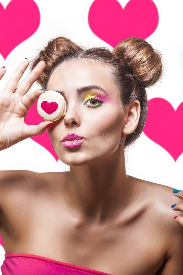 Mooi mannequinmeisje met koekjes met harten op roze bedelaars stock foto