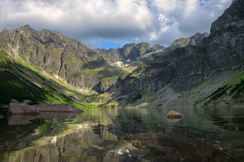 Mooi meer die op omringende bergen wijzen stock fotografie
