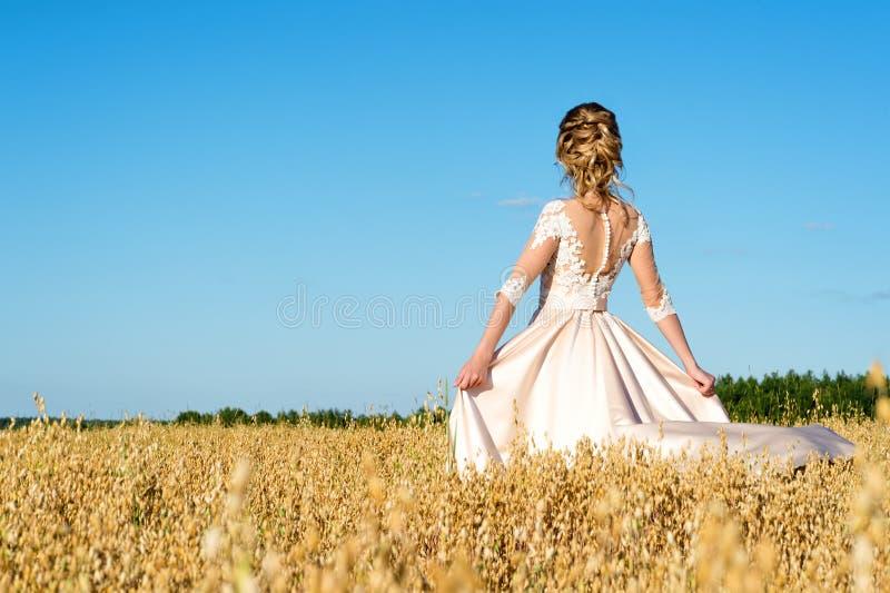 Mooi meisje in beige kleding in gebiedsrogge, achtermening stock foto's