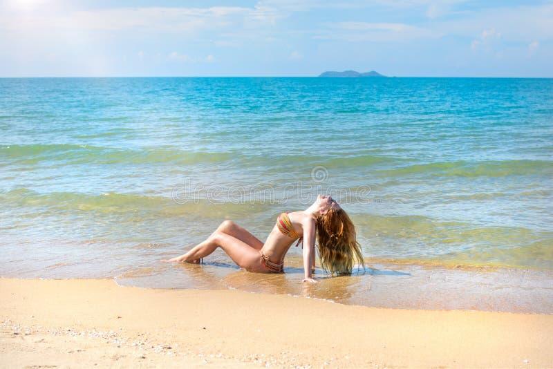 Mooi meisje in bikini het stellen op een verlaten strand wit zand, turkooise overzees en een jong meisje stock fotografie