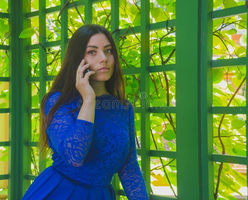 Mooi meisje in blauwe kleding die op de telefoon spreken royalty-vrije stock afbeelding