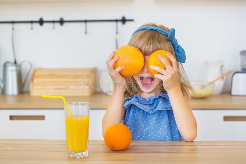 Mooi meisje in blauwe kledings grappige spelen met twee sinaasappelen thuis stock afbeeldingen