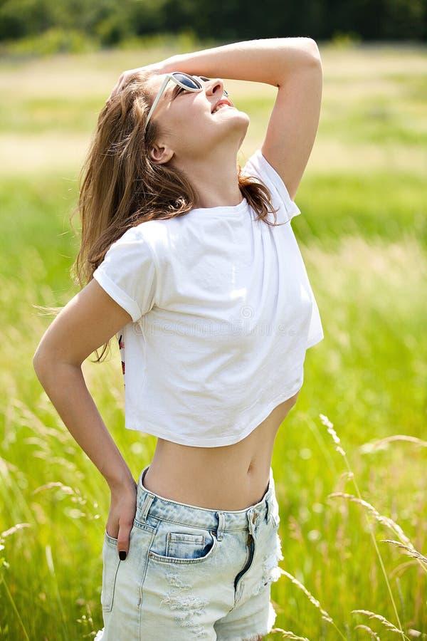 Mooi meisje in borrels en een t-shirt op het gebied onder het gras royalty-vrije stock afbeeldingen