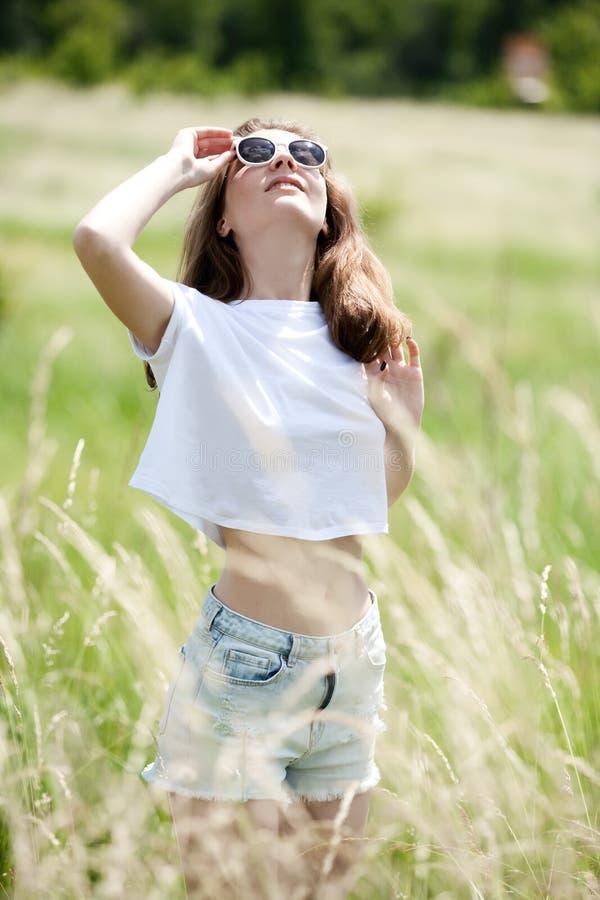 Mooi meisje in borrels en een t-shirt op het gebied onder het gras royalty-vrije stock fotografie