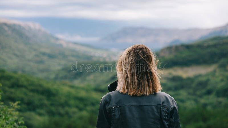 Mooi meisje bovenop berg het letten op landschap stock fotografie